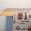 Pure 100% linen table runner. Handmade table linen. Kitchen accessories and tools pattern on grey.